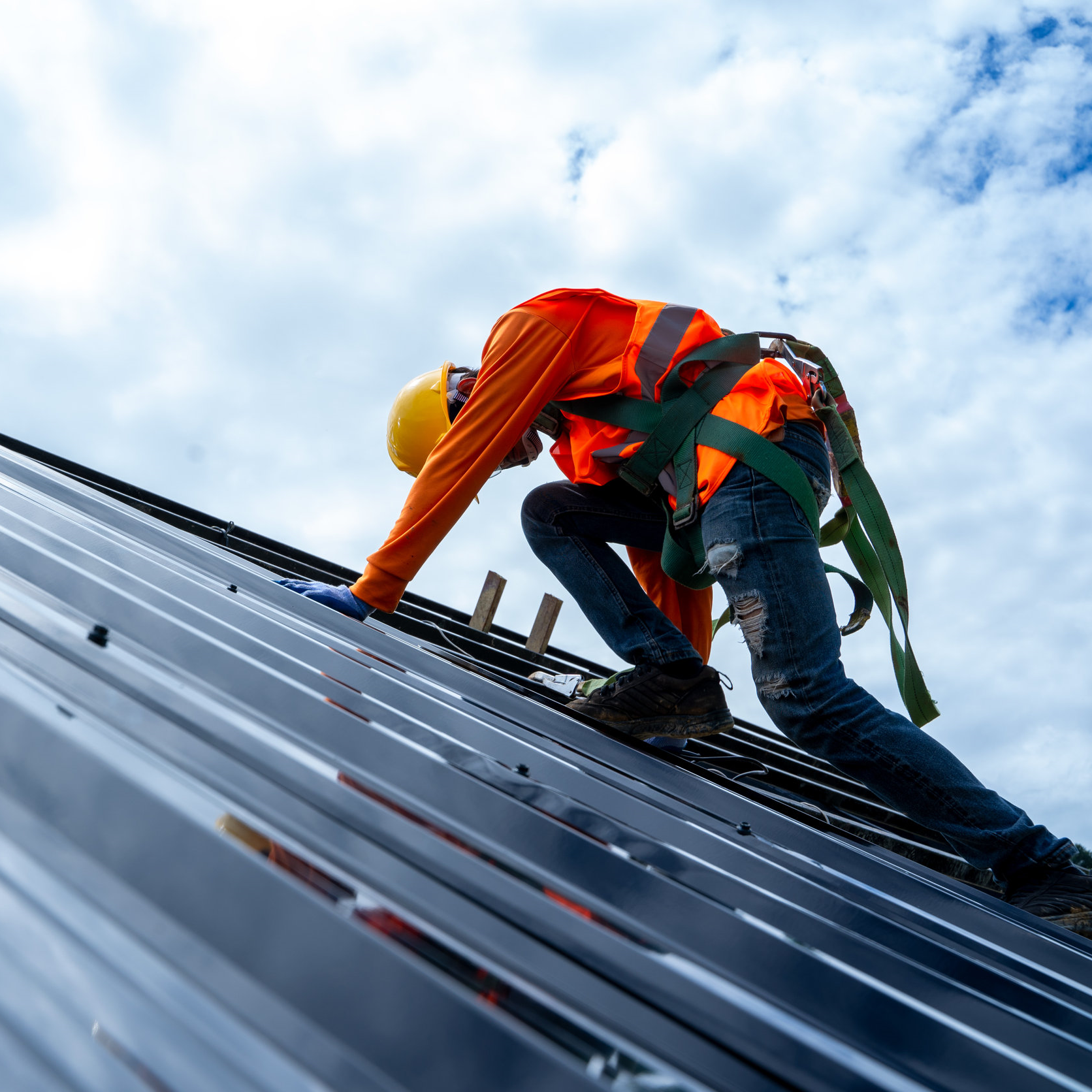 A Roofer Works on a Metal Commercial Roof.