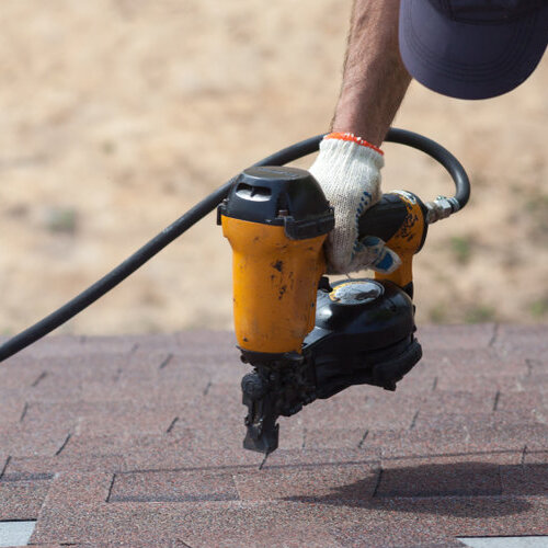 A Residential Roofer Nails Shingles.
